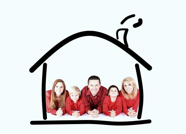 rodina v červeném oblečení pod načrtnutým domkem