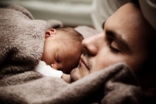 dítě leží na posteli vedle otce